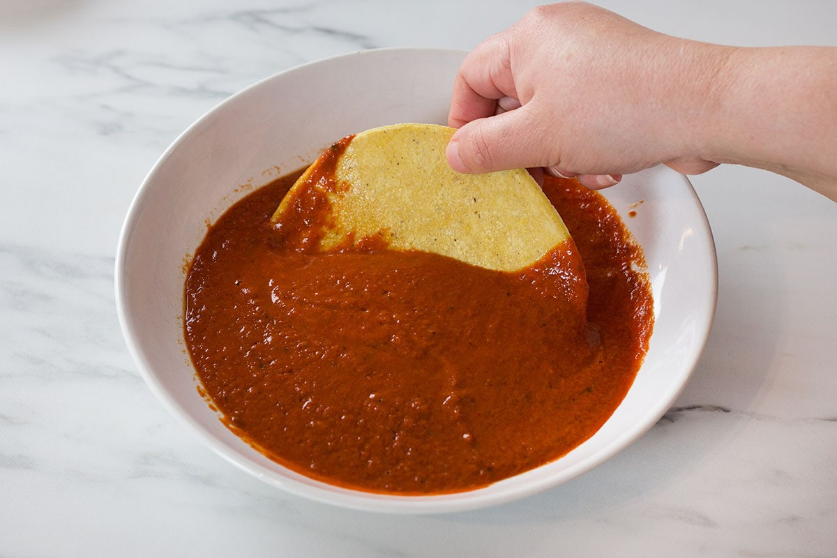 Soaking a tortilla in the enchilada sauce.