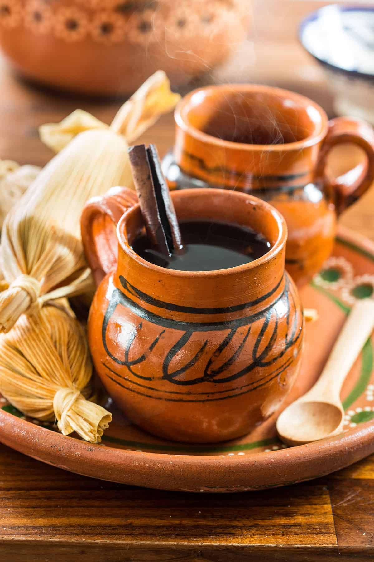 Two clay mugs with steamy café de olla.
