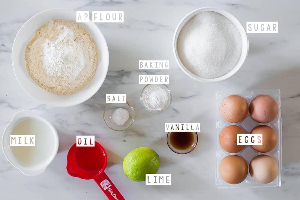 Gli ingredienti per la torta sopra una superficie di marmo e con i nomi di ognuno in inglese.