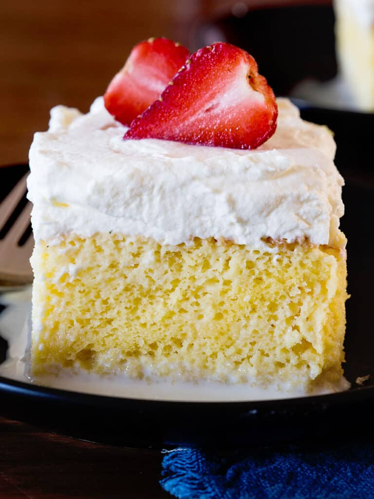 Una fetta di torta tres leches decorata con panna montata e una fragola.