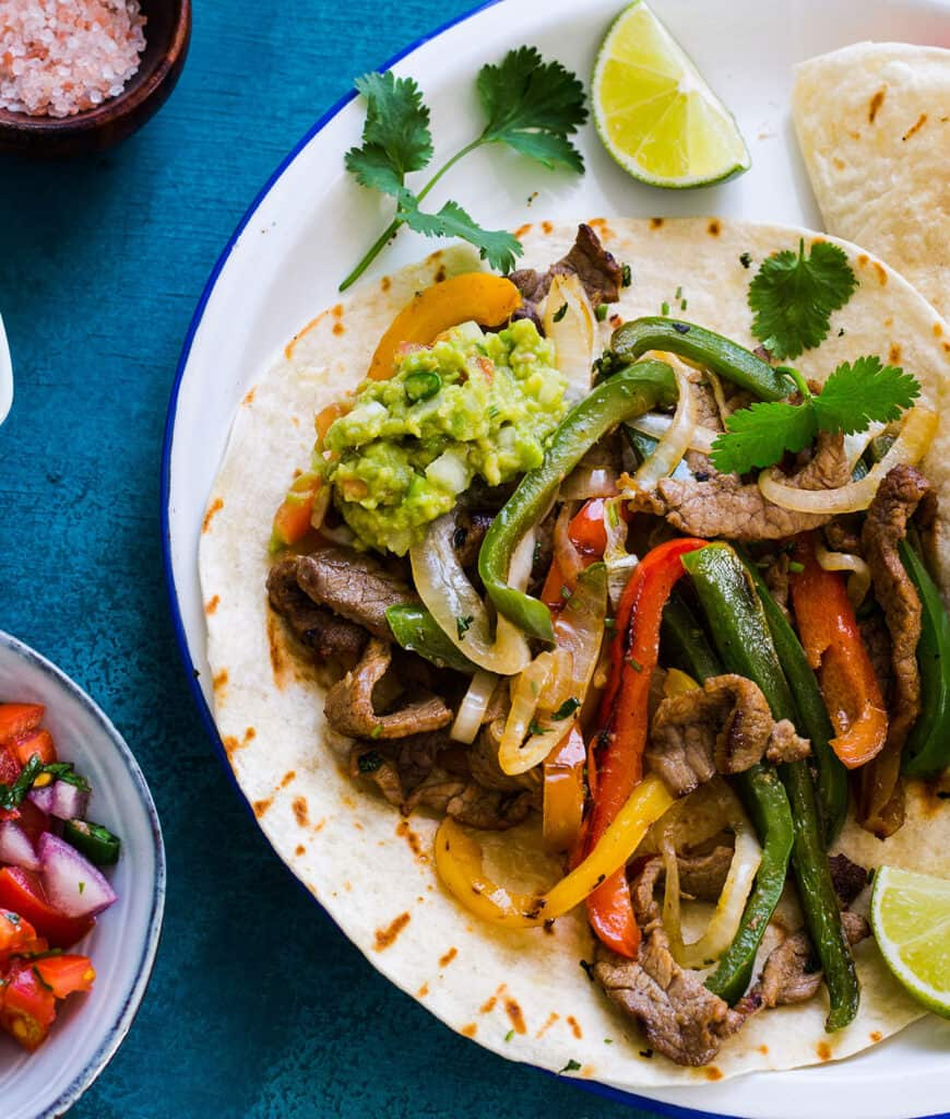 Flank Steak Fajitas served with flour tortillas to make a taco.