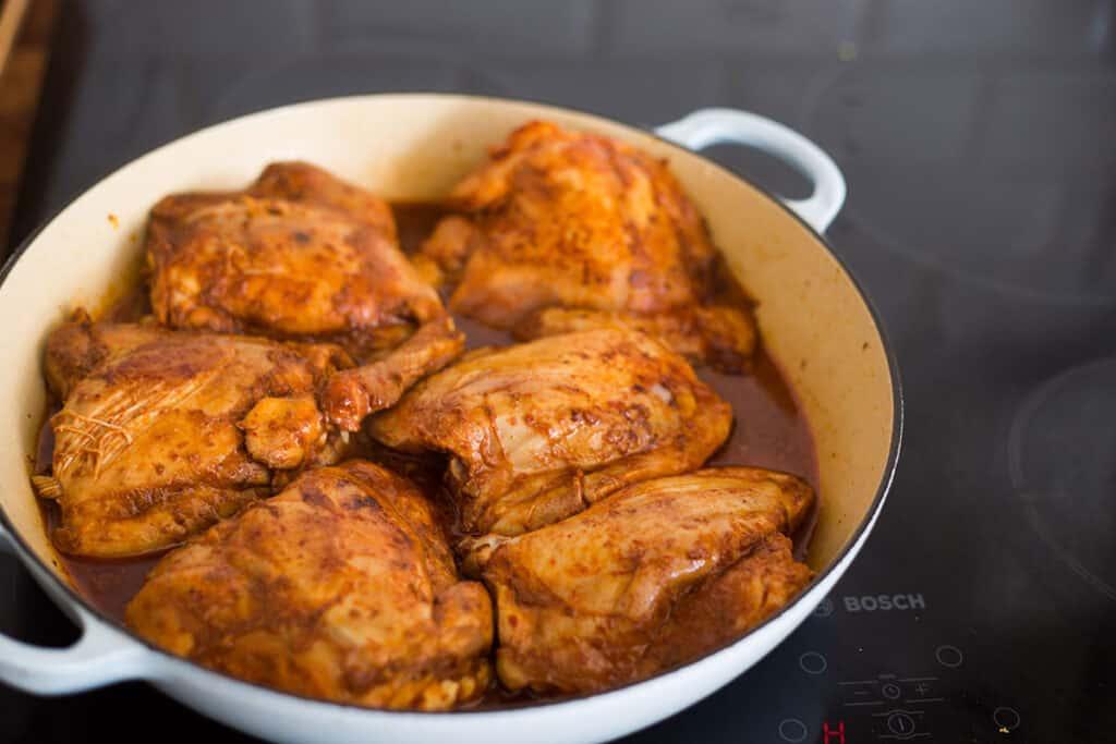 El pollo cocinándose con un poco de jugo en la cazuela.