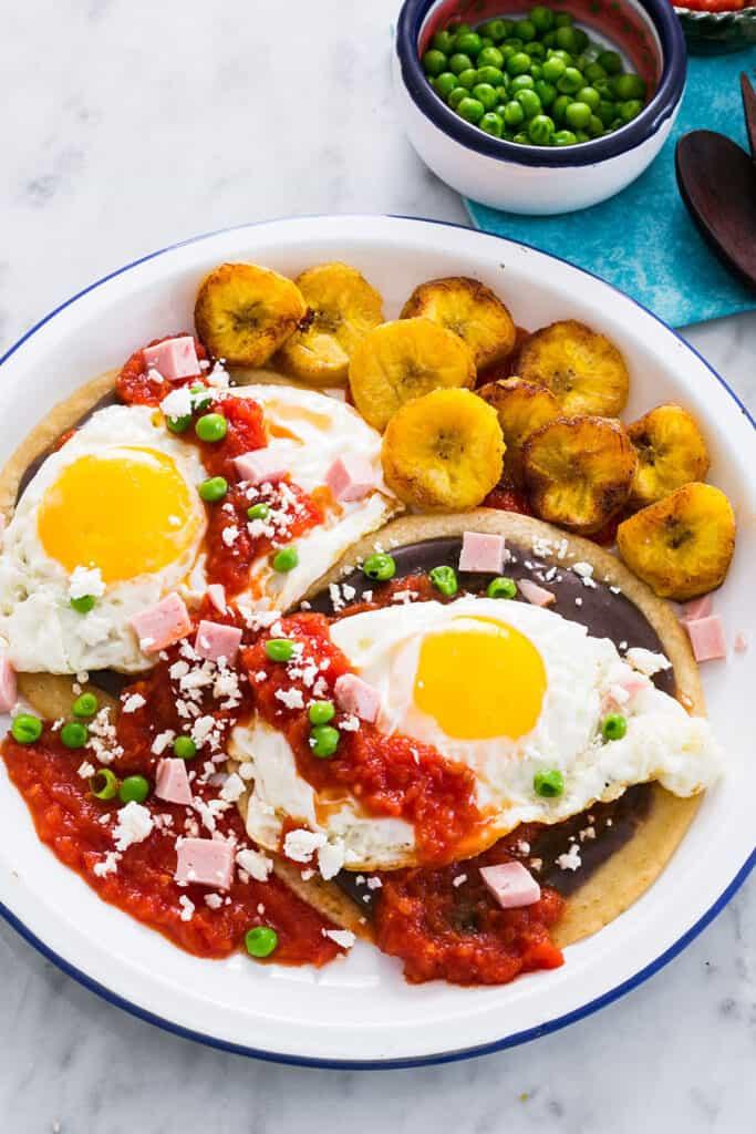 Huevos motuleños served on a white plate.