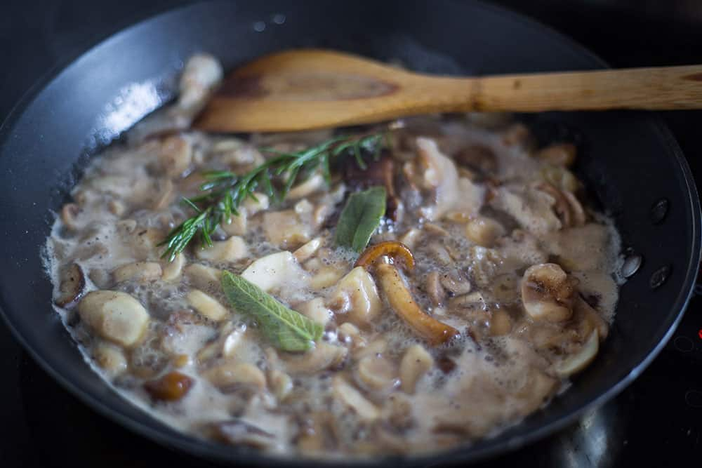 Sauteeing mushrooms with herbs on a pan.