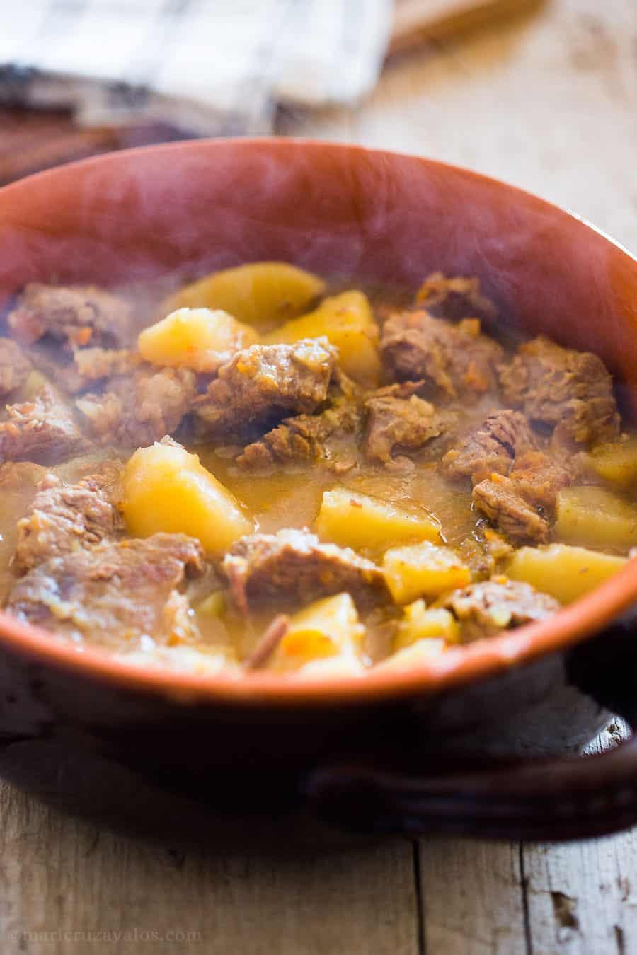 Spezzatino con patate dentro un tegame di coccio.