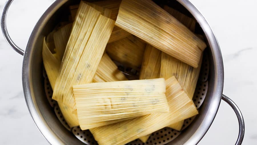 Tamales piled inside a steamer.