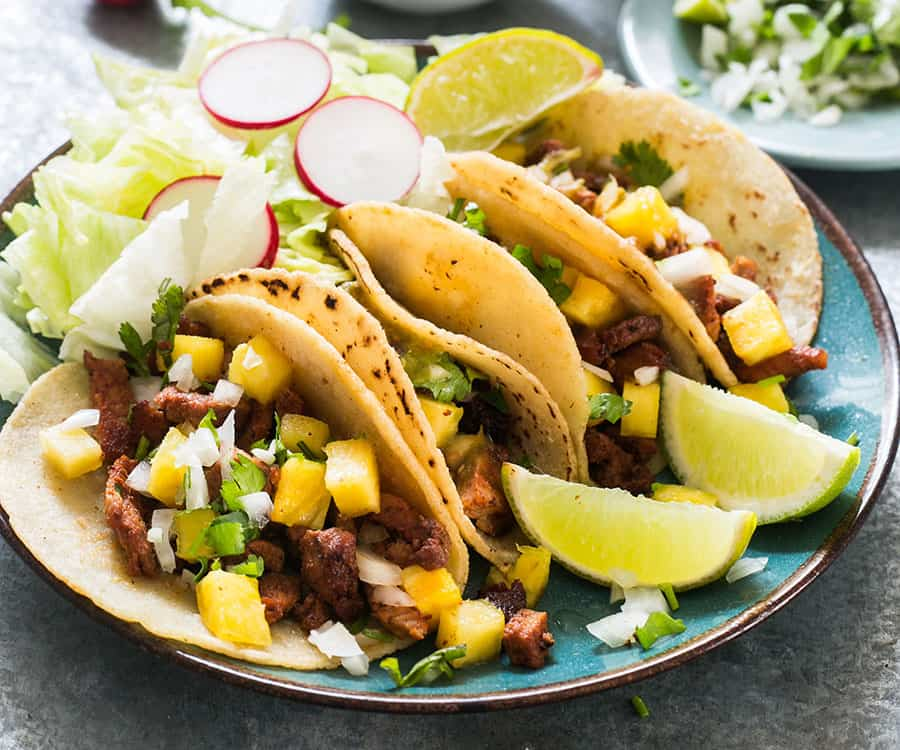 Tacos al pastor (pork tacos) served on corn tortillas and various toppings.