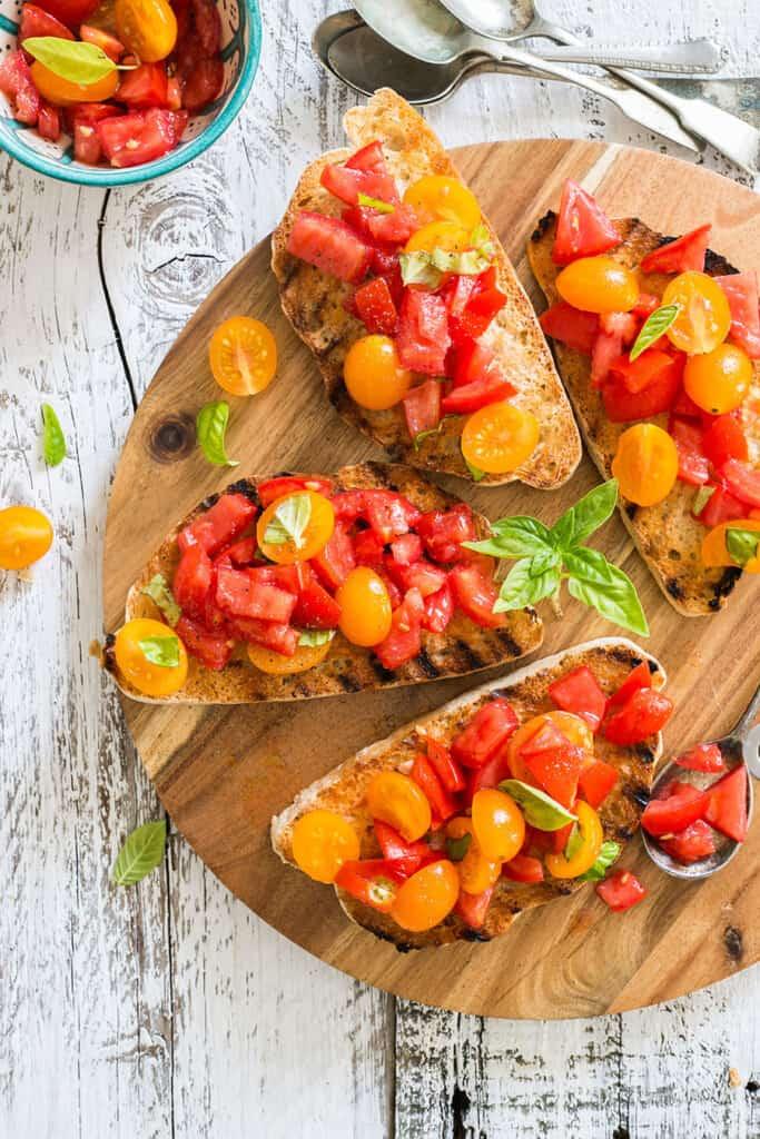 Various bruschetta al pomodoro on a cutting board.