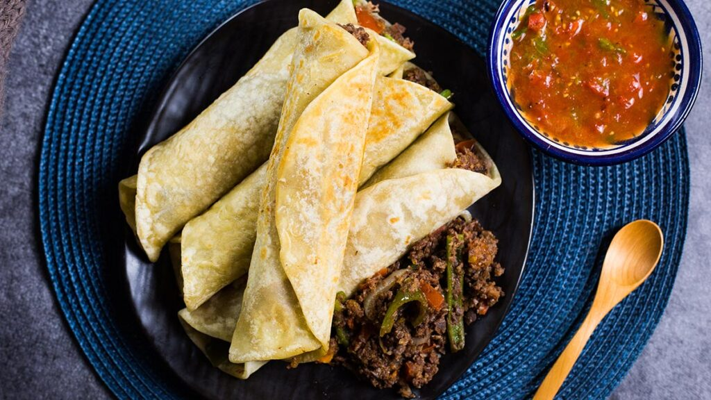 Burritos made with machaca and served with salsa.