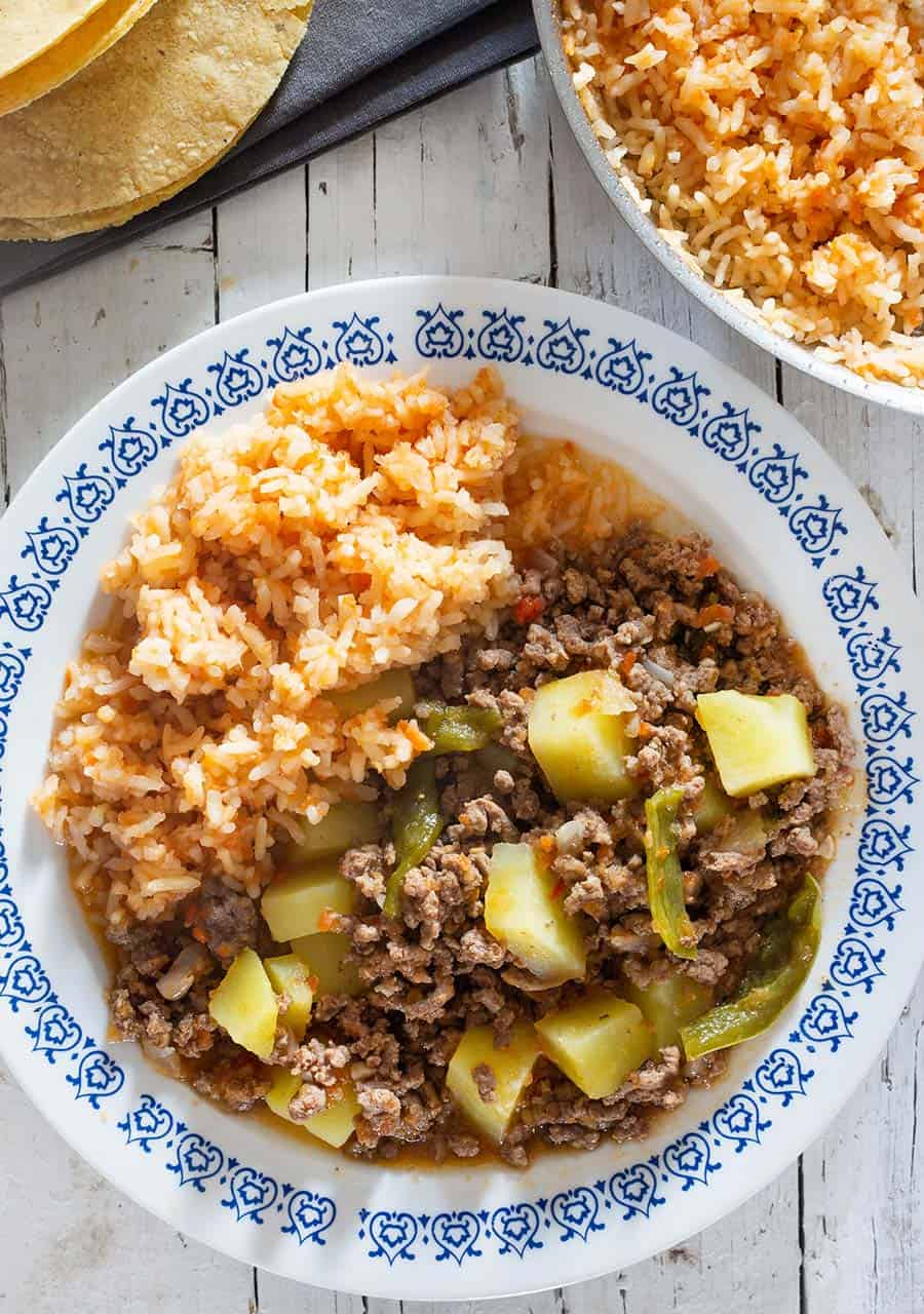 A plate with mexican picadillo and spanish rice as side dish.