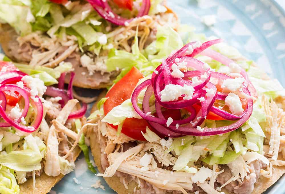 Chicken tostadas topped with mexican pickled onions.