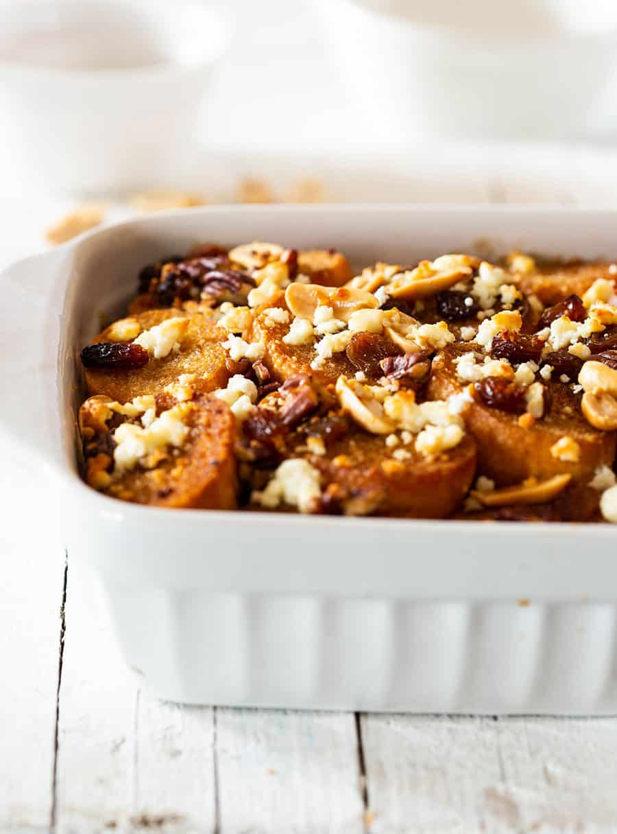 Side view of mexican bread pudding capirotada on a white baking dish.