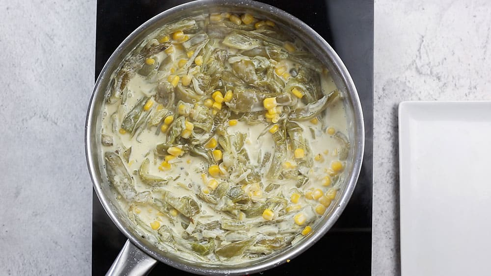 Cooking the rajas con crema on a pan.
