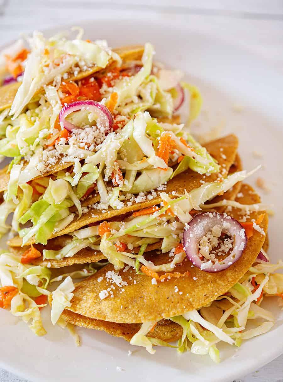 Tacos dorados de papas servidos con ensalada de repollo y zanahoria.