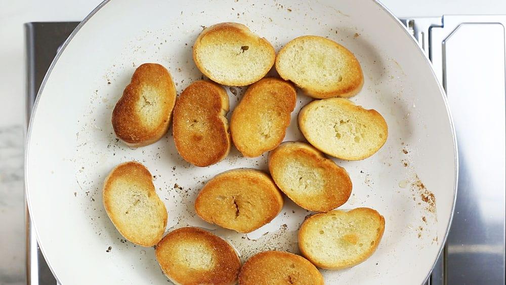 Friendo el pan en una sartén blanca.