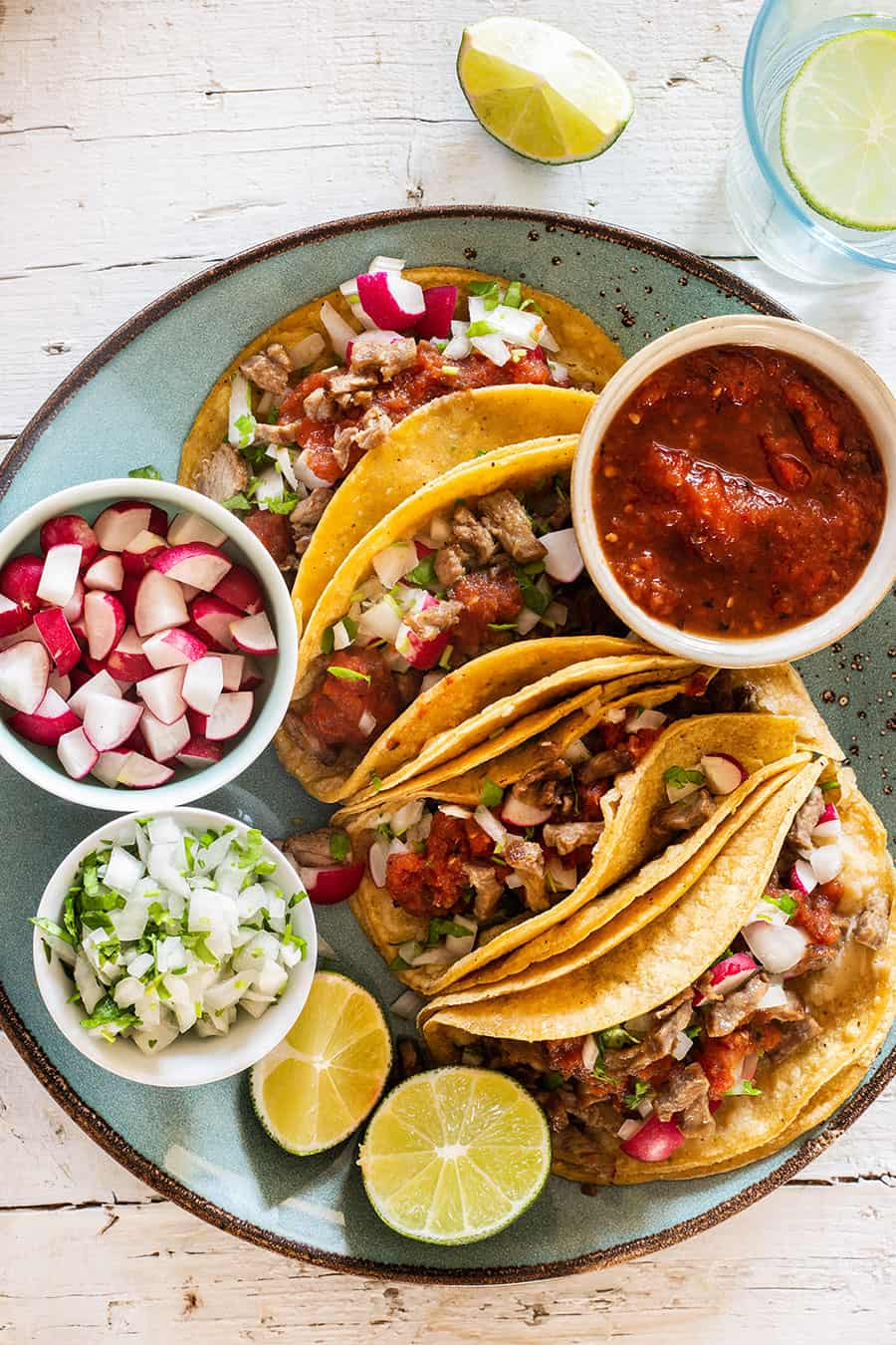 Steak tacos served on a turquoise plate with various toppings.