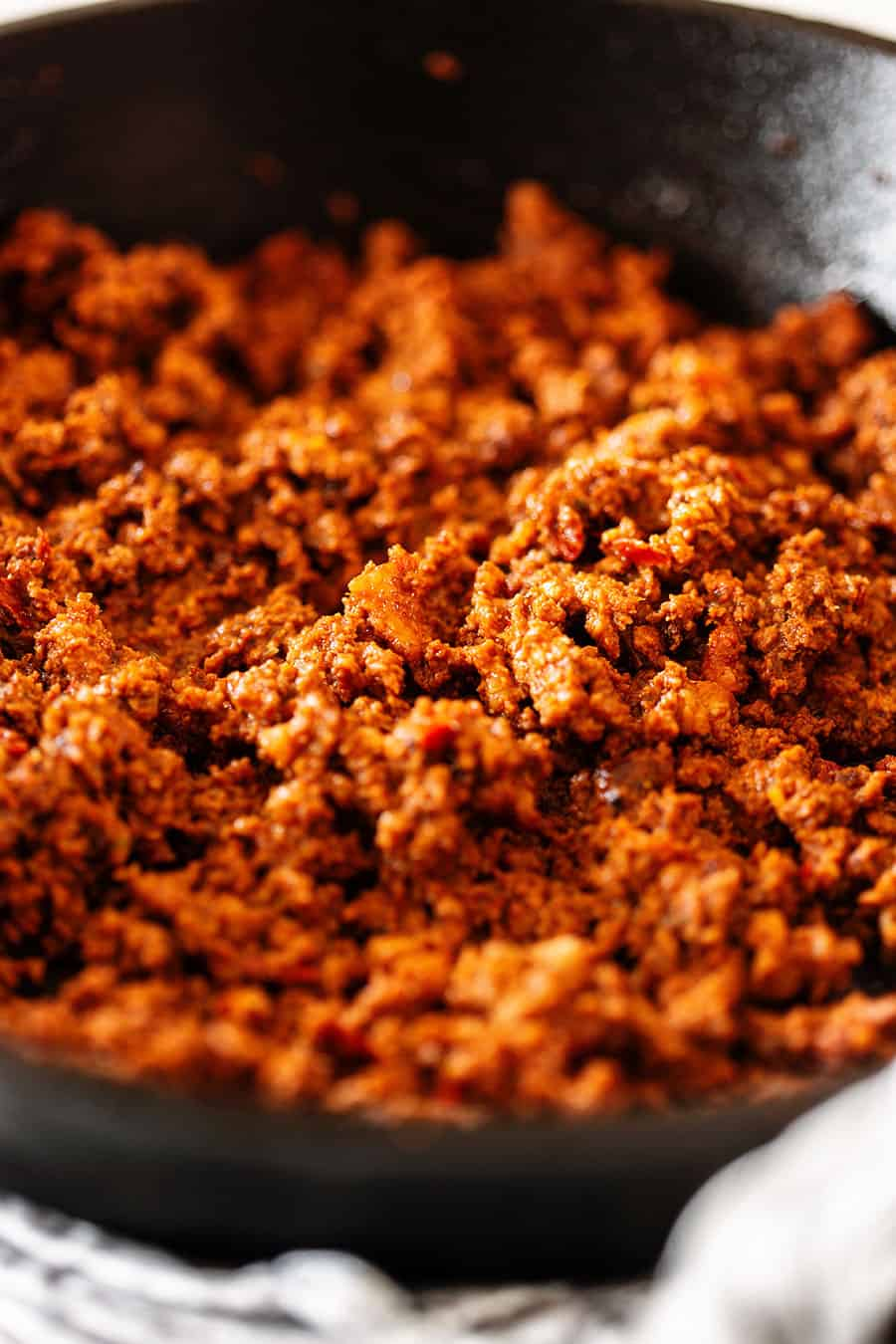 Fried chorizo on an iron-cast skillet.