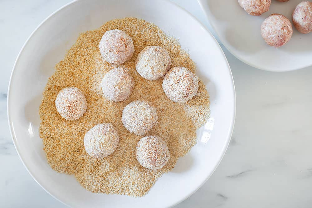 The italian meatballs coated with breadcrumbs on a plate.
