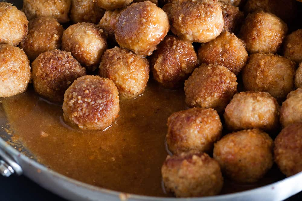The meatballs with some sauce on the bottom of the pan.
