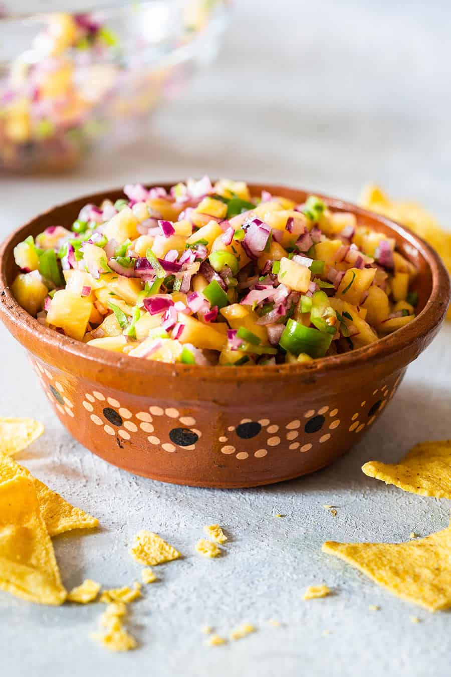 Pineapple salsa with jalapeno served on a Mexican clay bowl.