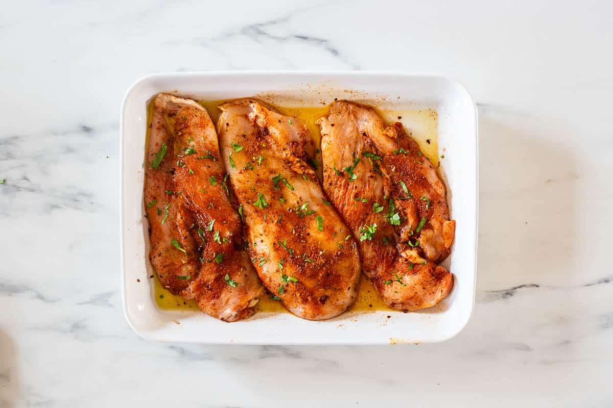 The chicken breasts seasoned with fajita seasoning on a baking dish.