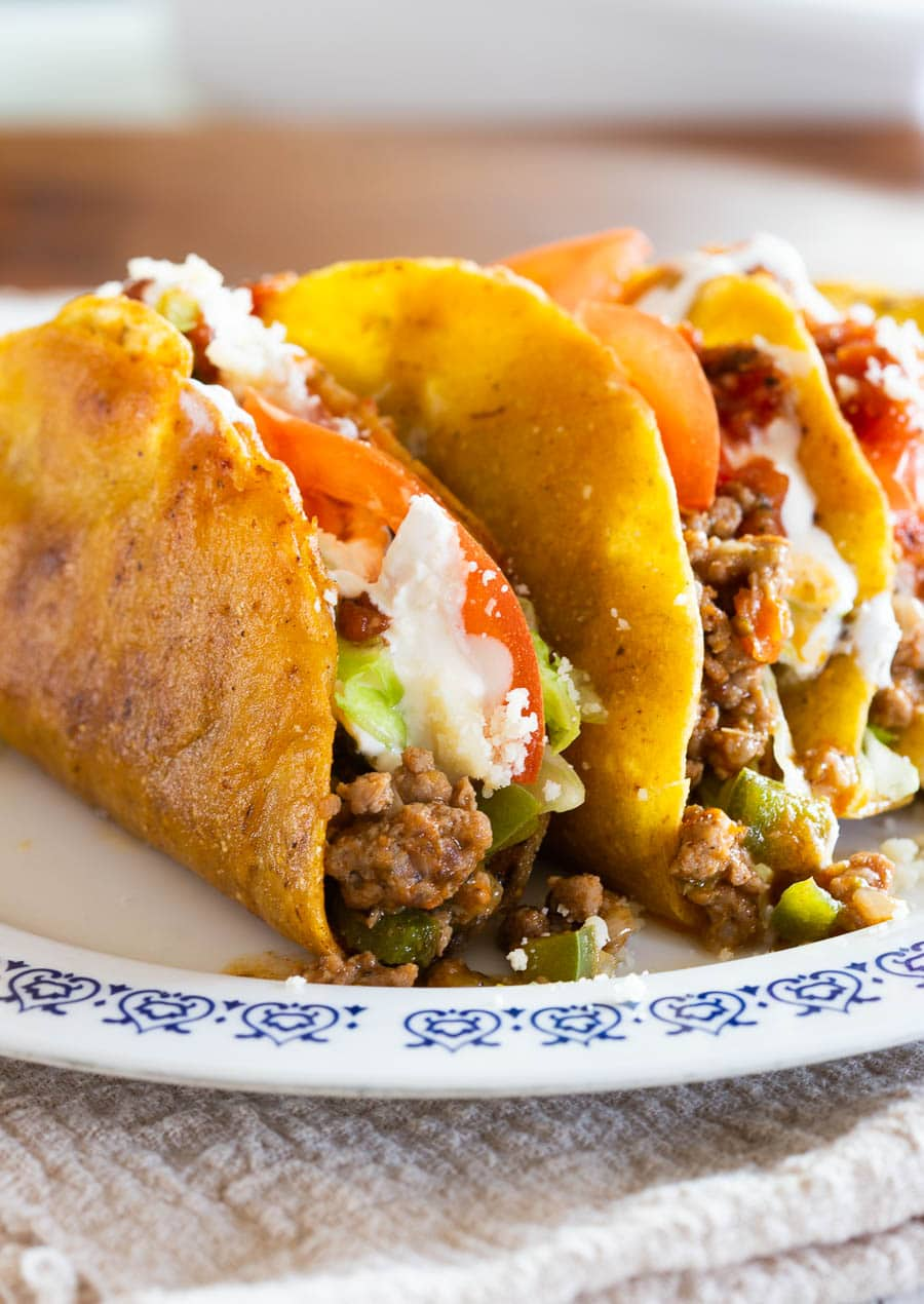 Mexican picadillo tacos served with various toppings.