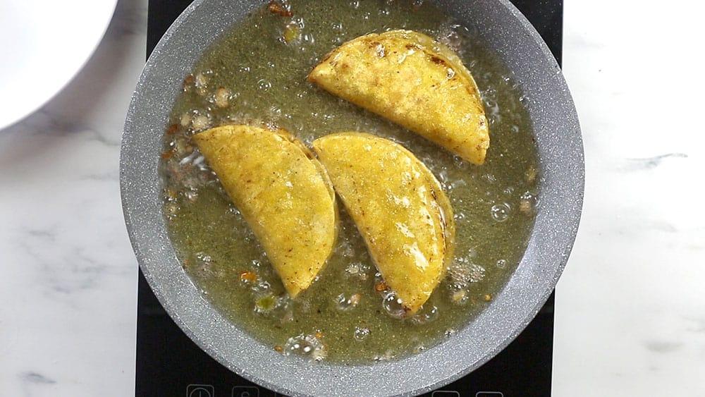 Frying tacos in hot oil.