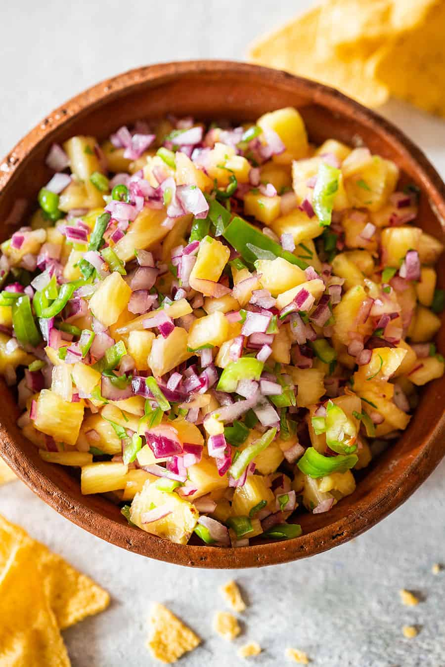 A clay bowl loaded with pineapple jalapeno salad.