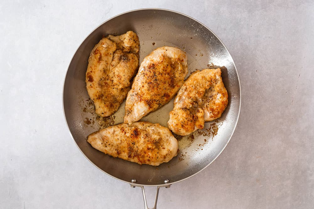 Pan fried chicken on a pan.