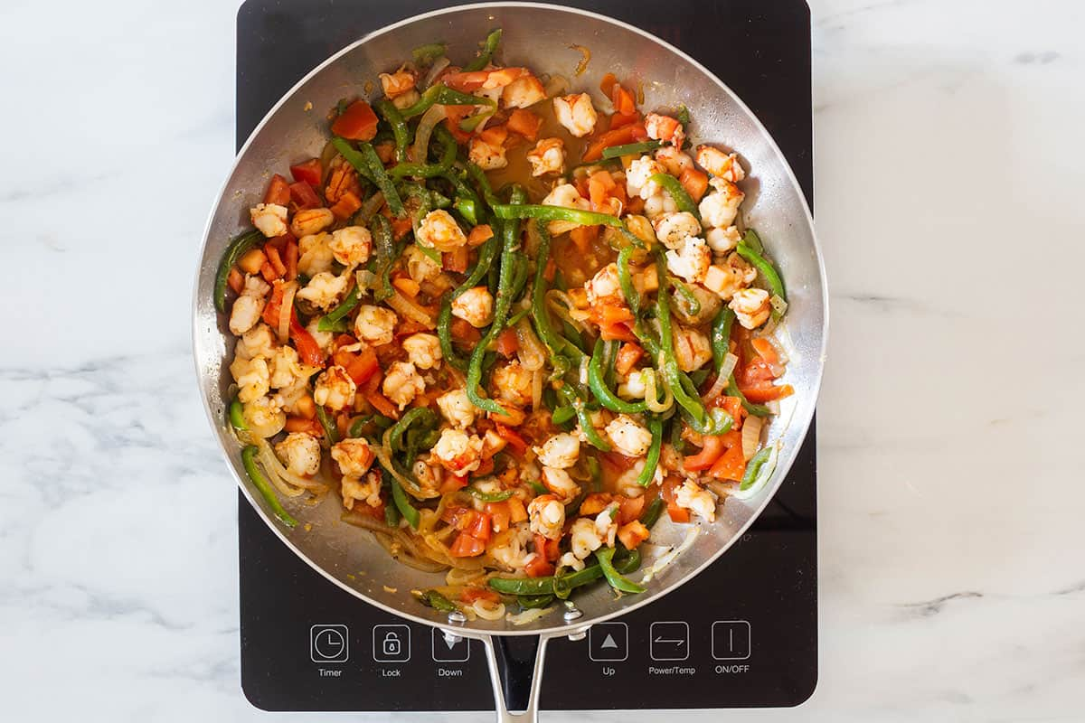Sauteeing shrimps with all vegetables on the pan.