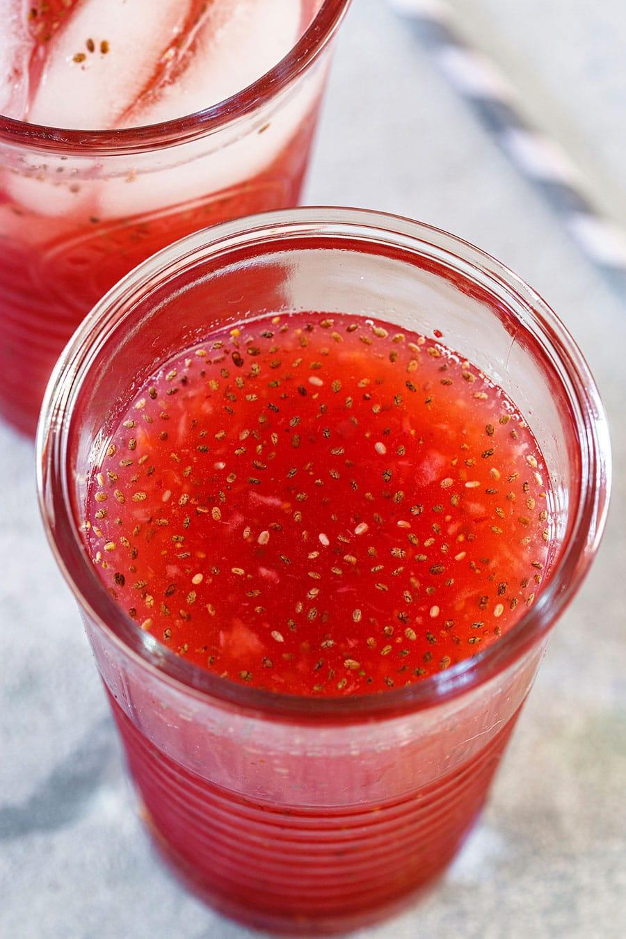 A close up of agua de fresa in a glass.