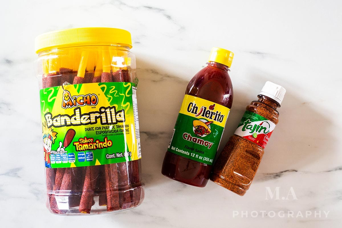 Banderilla candies, Chamoy sauce and Tajín powder on a marble surface.