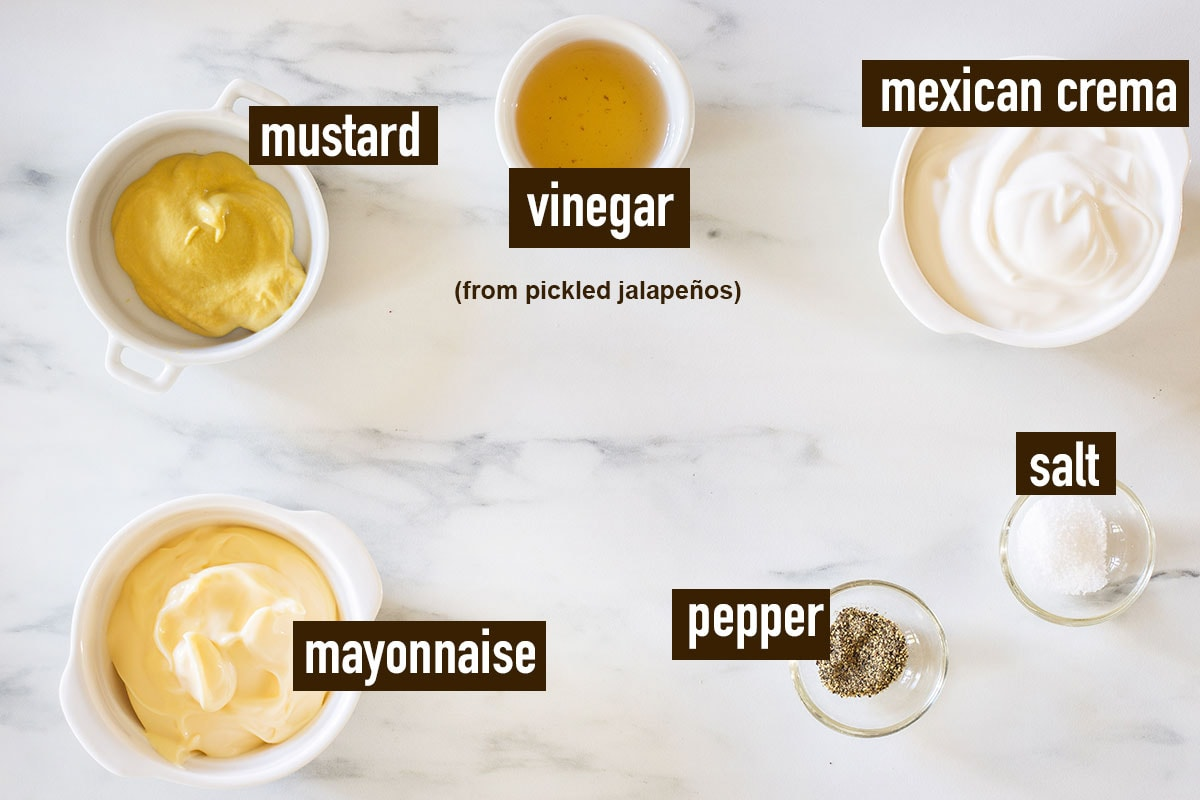 The dressing ingredients labeled and displayed on a marble surface.
