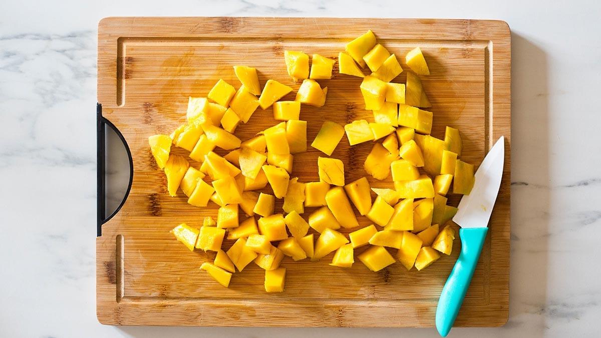 Fresh mango cubes on a cutting board.