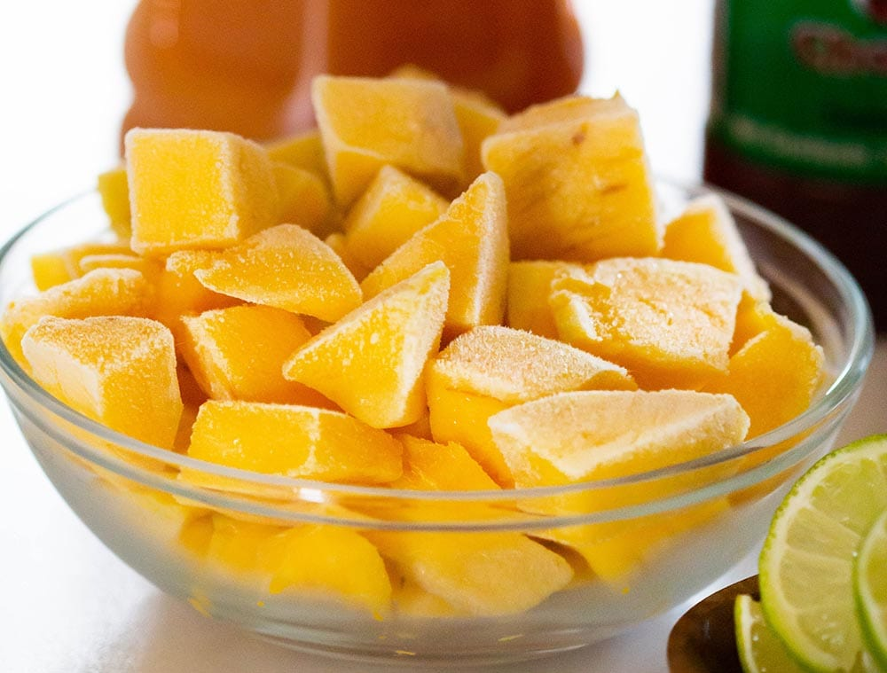 Frozen mango cubes in a bowl.