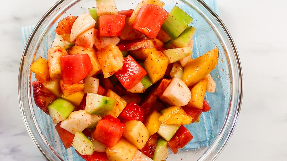 The fruit seasoned and mixed on a bowl.