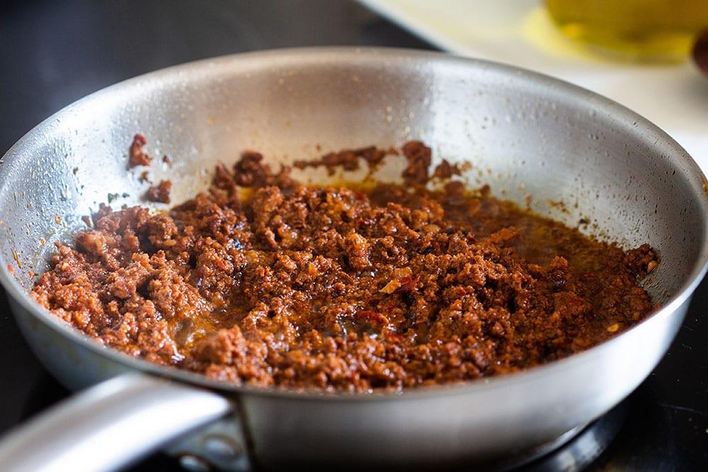 Frying chorizo on a pan.