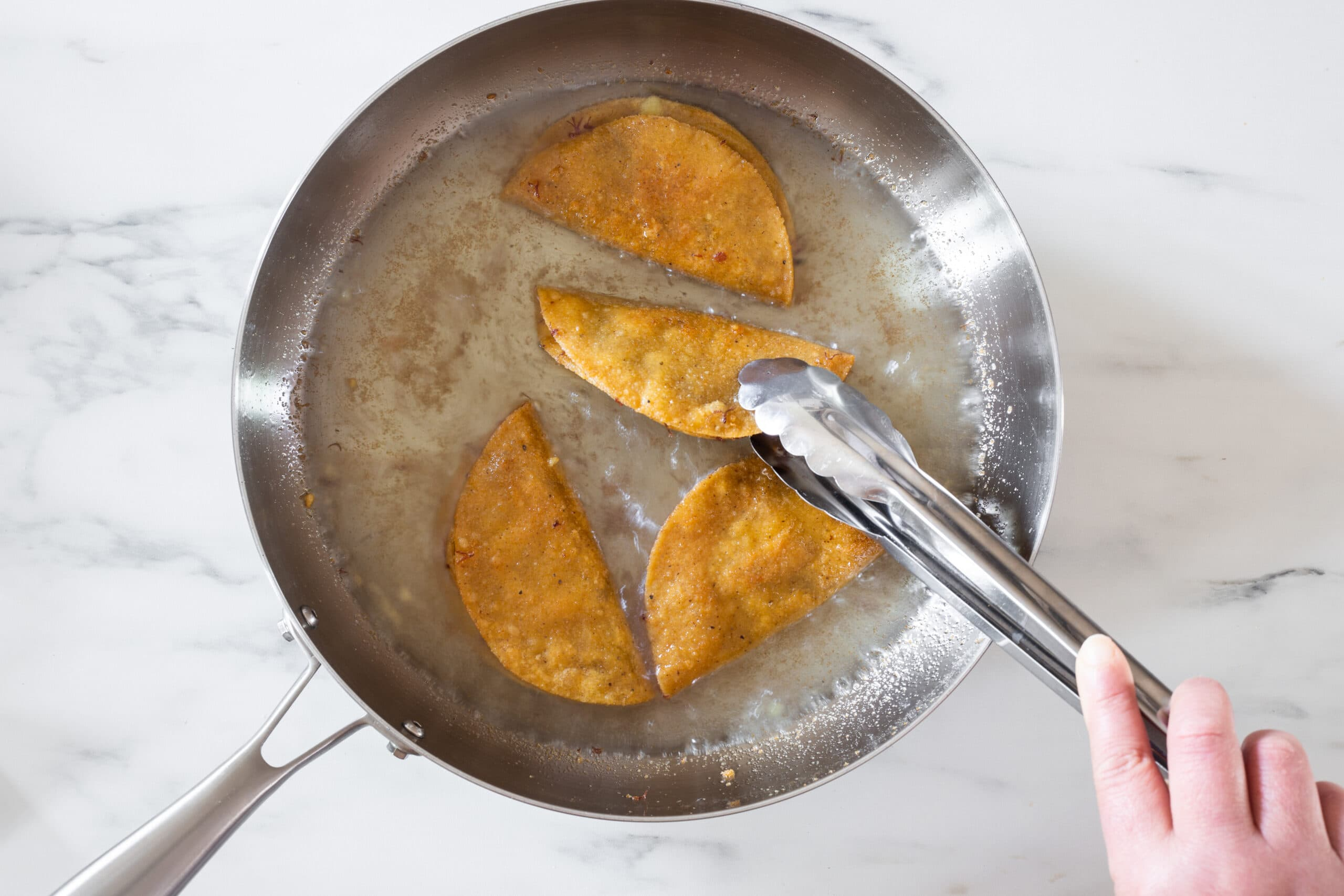 Frying tacos on a pan.