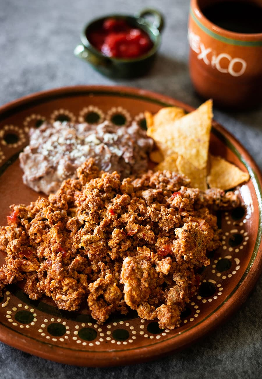 Huevos con chorizo served on a Mexican clay plate with fried beans and corn chips on the side.