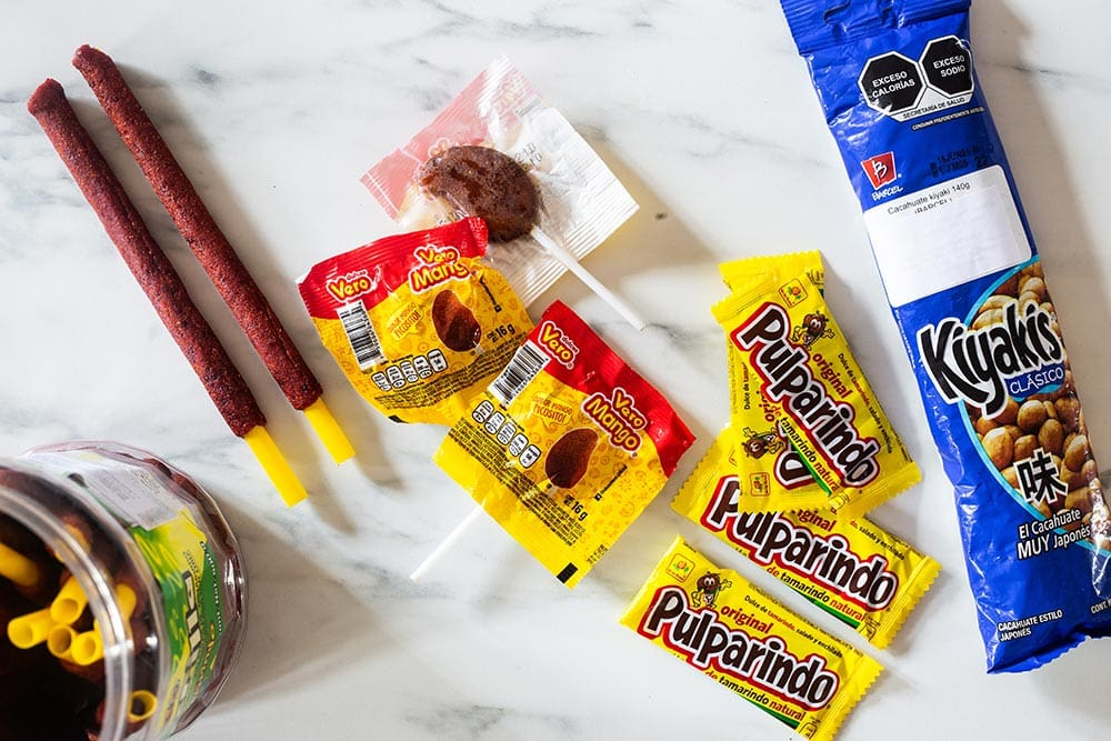 A variety of Mexican candies displayed on a marble surface.