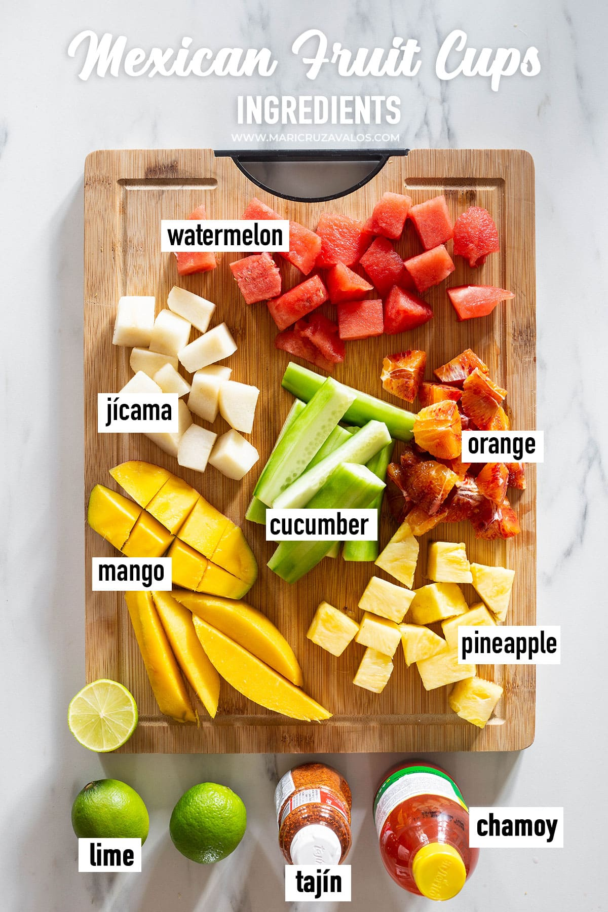 A cutting board loaded with various tropical fruits cut into pieces.