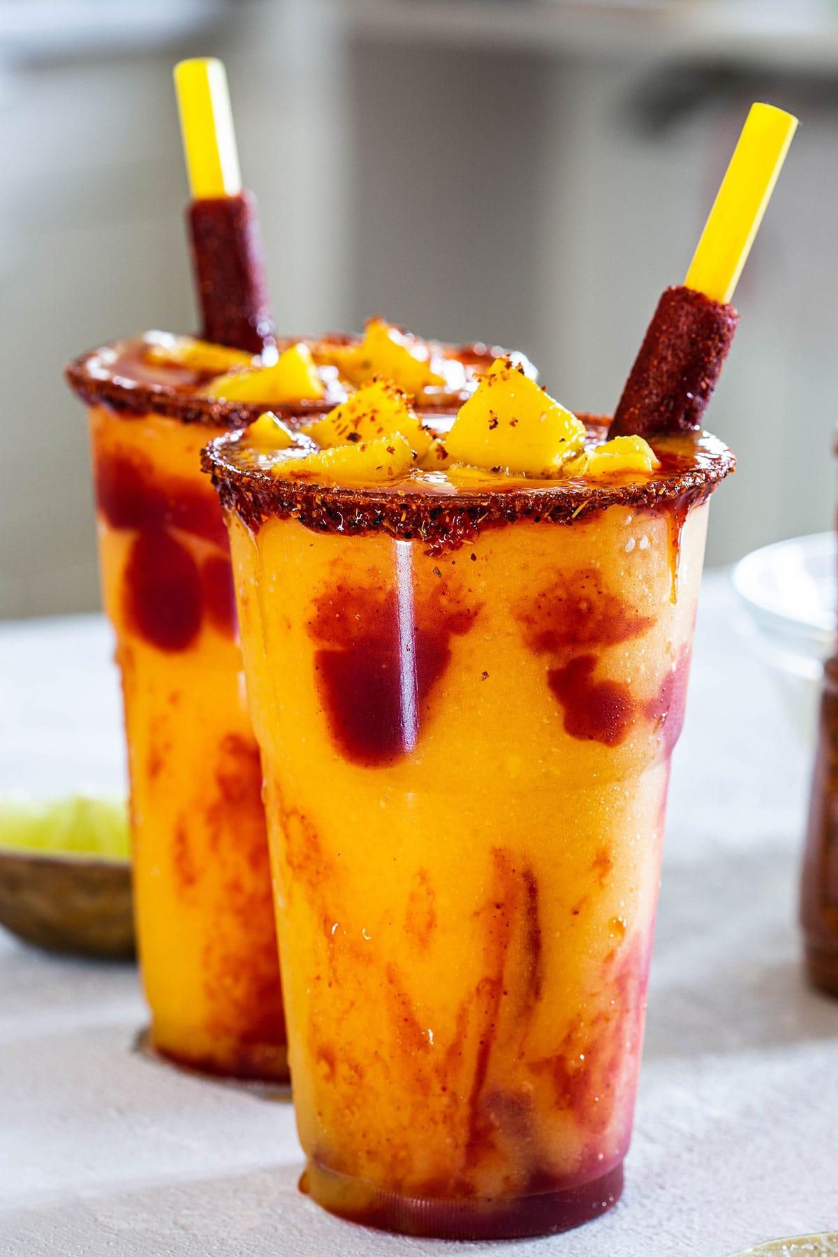 Two glasses with mexican mango frozen treat called mangonadas or chamoyadas.