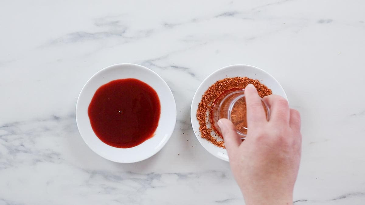 Dipping a glass into chili powder.