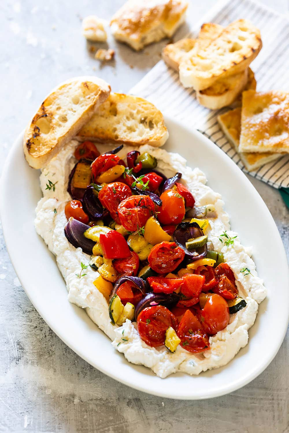 A platter of whipped ricotta with roasted vegetables on top.