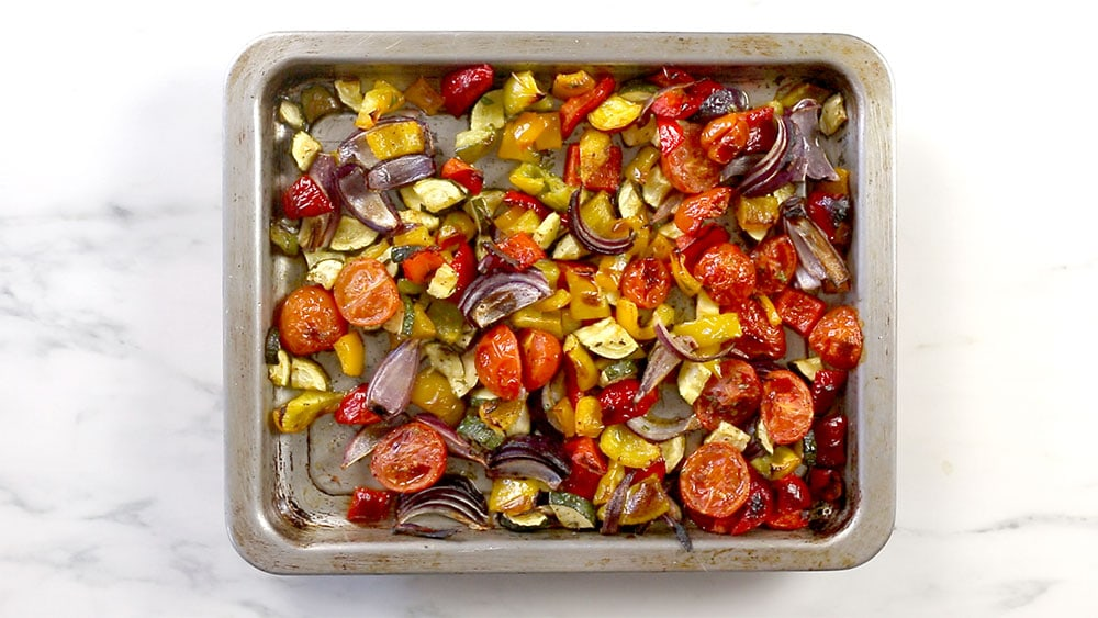 A baking tray with roasted vegetables.