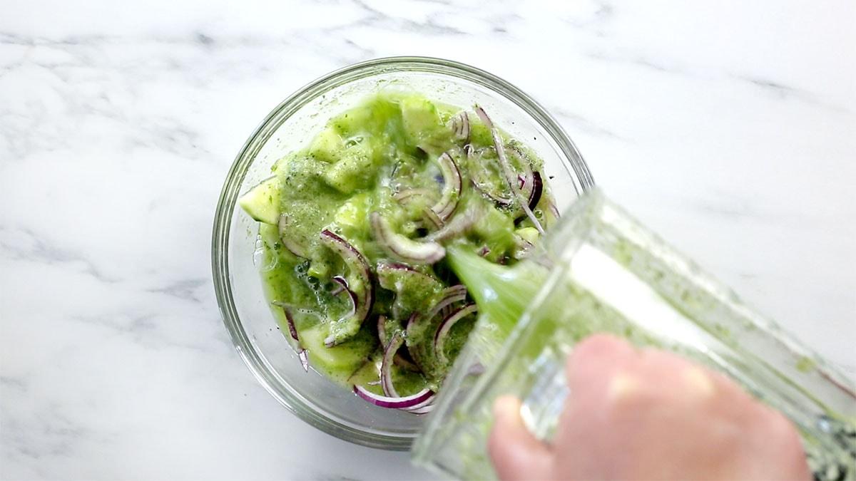 Adding salsa verde over vegetables and shrimps on a bowl.