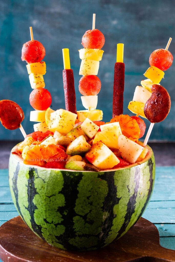 Sandia loca (crazy watermelon) decorated with fruit skewers and Mexican candies.
