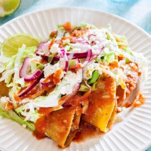 Tacos dorados (crispy tacos) with various toppings.