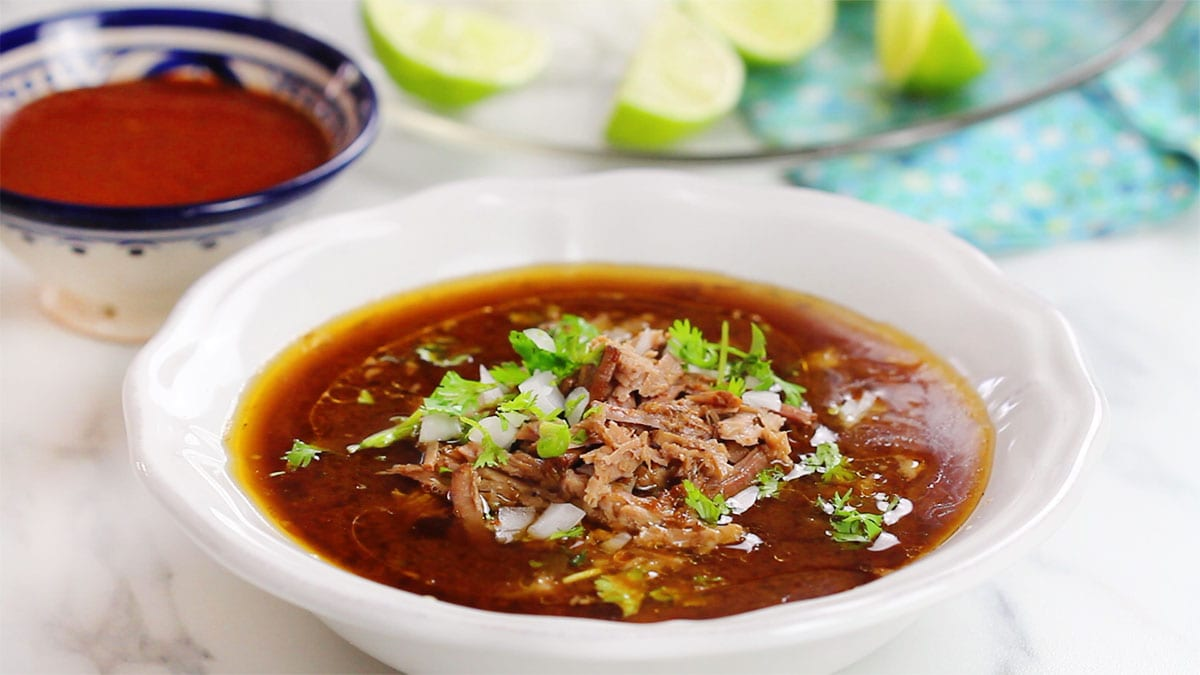 Beef birria served on a deep plate and garnished with cilantro and onion.