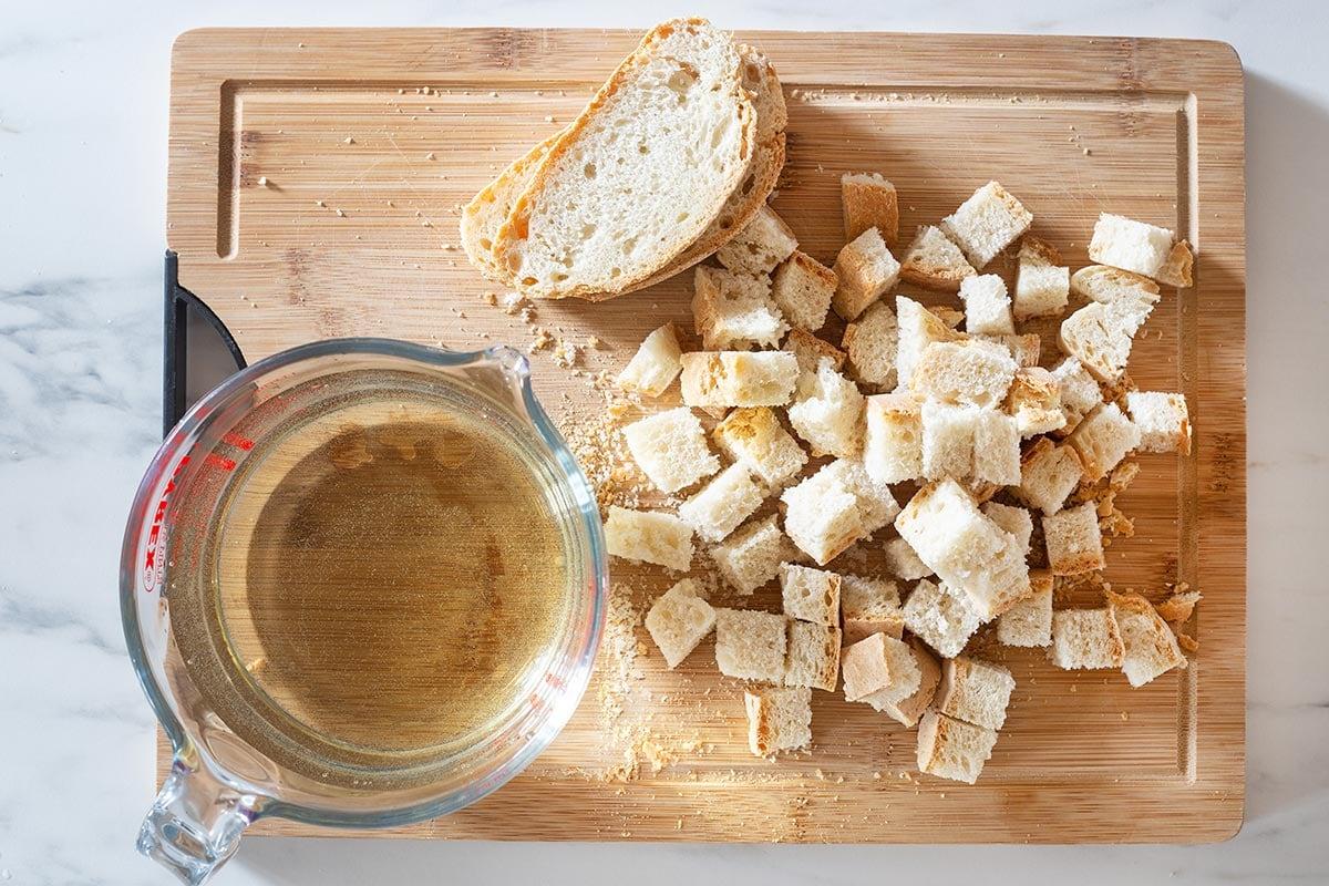 Crusty bread cut into cubes on a cutting board.